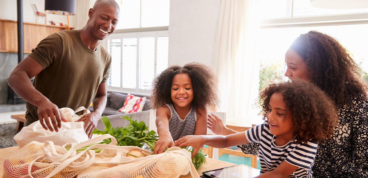 Image of a happy family laughing and unpacking groceries at home.